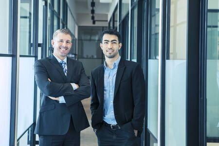 Fiduciosi uomini d'affari multietnici in piedi in un corridoio di ufficio