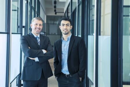 Zuversichtliche multiethnische Geschäftsleute, die in einem Bürokorridor stehen