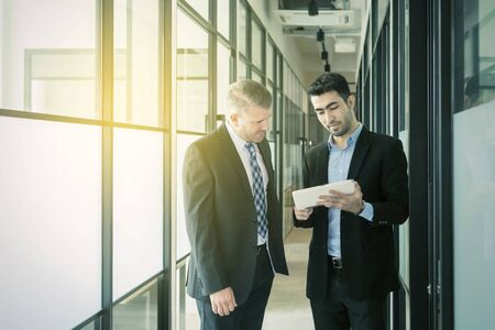 Two serious businessmen talking and looking at tablet computer while standing in office corridor