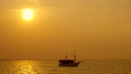 Silhouette of vintage sailboat sailing along the sea with a golden sunrise Standard-Bild