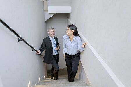 Coworkers talking on the stairs of an office