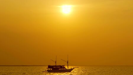 Silhouette of vintage sailboat sailing along the ocean with golden sunset