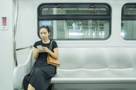 Asian woman using mobile phone in jakarta LRT Train