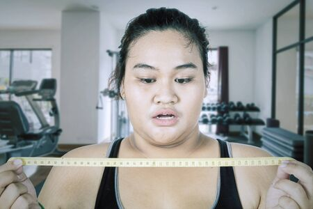 Fat Asian woman wearing sportswear while feeling shocked after seeing her body checkup in the gym center