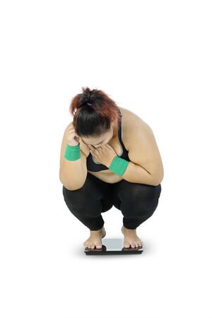 Unidentified fat woman wearing sportswear while squatting down to her knees due to her increasing body weight, isolated in white background