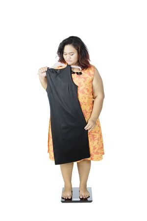Fat Asian women wearing old blouse while holding and staring at her old dress with a gloomy face, isolated in white background Stock Photo