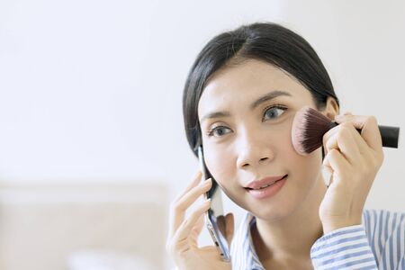Beautiful Asian businesswoman holding a blush brush while talking on the phone getting ready for work