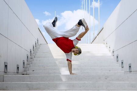 Overweight Street Bboy dancer wearing hat and headphone doing handstand on stairs