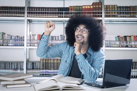 Handsome black man with big afro hair exclaims with amazement in library. Aha moment concept