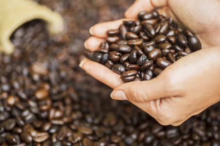 Focused view of a grasp of coffee beans from the little sack, shrouded by handful of other coffee beans