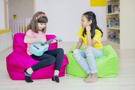 Two multiethnic pupils learning to play ukulele by changing turns each other while the Asian girl getting bored of waiting in the classroom