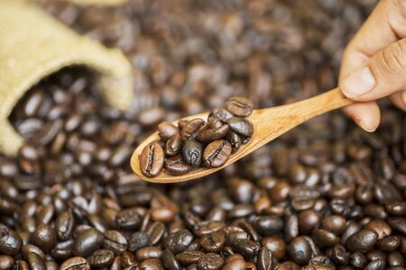 Focused view of a tiny wooden spoon of coffee beans from the little sack, shrouded by handful of other coffee beans