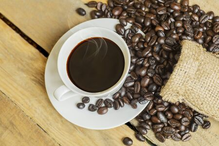 Top view of a served porcelain cup filled with brewed coffee from the other few scattered coffee beans on a wooden table