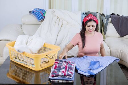 Portrait of beautiful Asian woman wearing pajamas while folding some clothes seriously in a living room full of laundries
