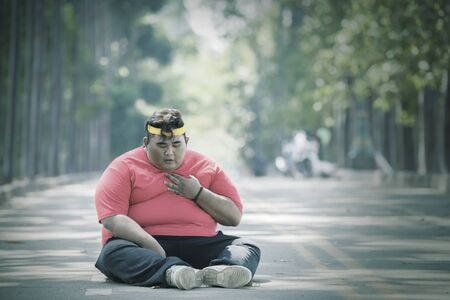 Focused view of fat Asian man wearing sportswear while patting his chest in the middle of the roads