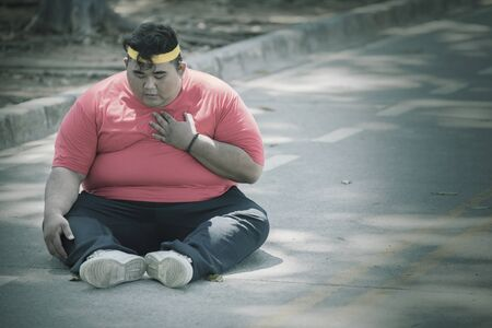 Fat Asian man wearing sportswear while patting his chest in the middle of the roads