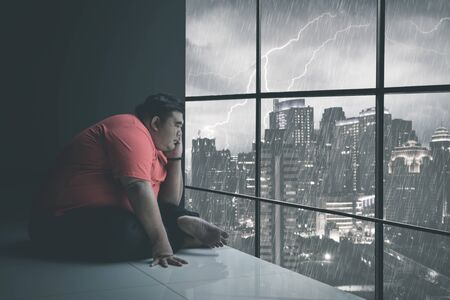Side view of fat Asian man holding his chin while staring at the raining city through the window somberly with raining cityscape background