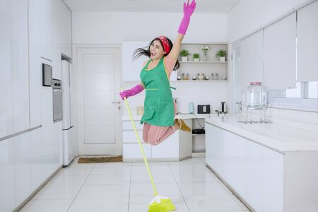 Beautiful Asian woman jumping happily and joyfully with her hairs flying while sweeping the floors in the kitchen