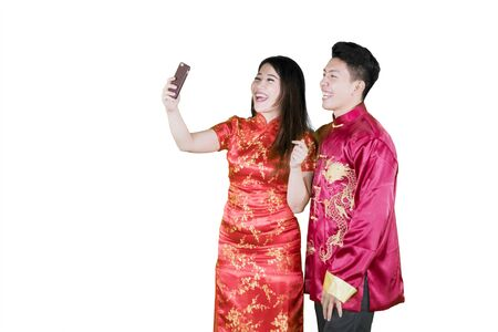Two Asian people wearing cheongsam while taking a selfie happily, isolated in white background