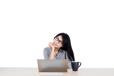 Portrait of beautiful Asian businesswoman musing and daydreaming while working on her laptop, isolated in white background