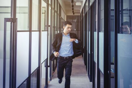 Handsome Asian businessman checking his watch while running on the office hallway