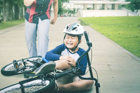 Adorable Asian boy crying because of his injured knee after falling from his bike while his father running and trying to help him at the park