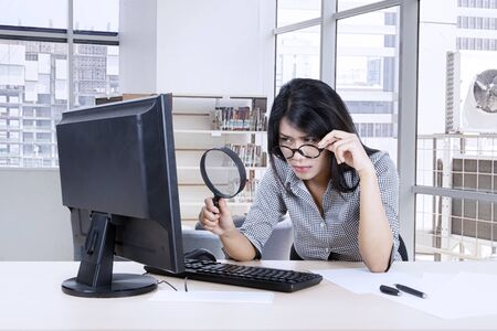 Portrait of beautiful Asian businesswoman holding her glass while examining some document at her desktop in her office with cityscape background