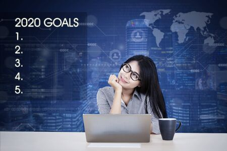 Portrait of beautiful Asian businesswoman musing and daydreaming while working on her laptop, isolated in business chart with night cityscape background