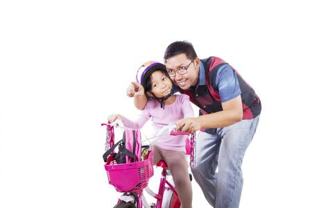 Adorable Asian girl going to school with her bicycle while being accompanied by her father, isolated in white background