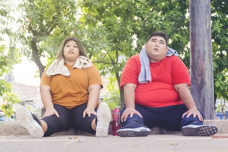 Fat Asian couple wearing sportswear, while taking a break after working out underneath the sunlight at the park