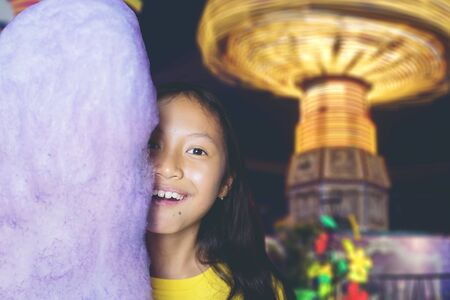 Portrait of adorable Asian girl smiling at camera, while hiding half of her face behind a huge cotton candy in an amusement park at night 版權商用圖片