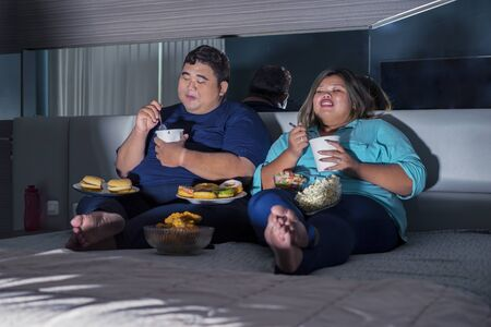 Fat Asian couple eating ice cream happily, while watching television with other junk foods scattered around them in their bedroom
