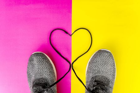 Top down view of heart shaped shoelaces, isolated in red and yellow background Zdjęcie Seryjne