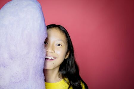 Portrait of adorable Asian girl smiling at camera cheerfully while hiding half of her face behind a huge cotton candy, isolated in red background