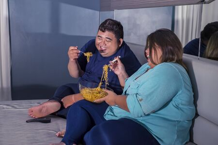 Fat Asian couple laughing at some television channel, while eating instant hot fried noodle in their bedroom Zdjęcie Seryjne