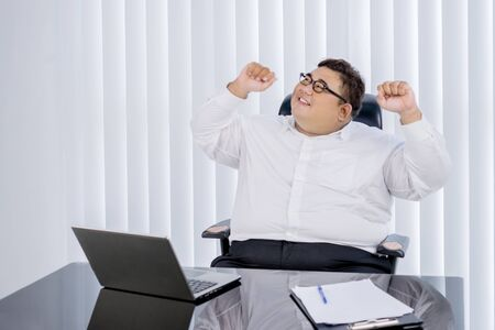 Portrait of fat Asian businessman wearing formal attire, while cheering for his finished work in his office
