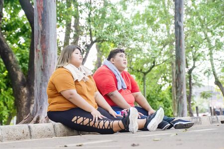 Fat Asian couple wearing sportswear, while taking a break after working out at the park