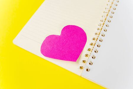 Closeup of heart shaped card on the middle of the notebook, isolated in yellow background Stock fotó - 138254298