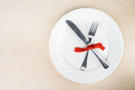 Top down view of fork and knife taped together with a ribbon on a plate, isolated in wooden table background