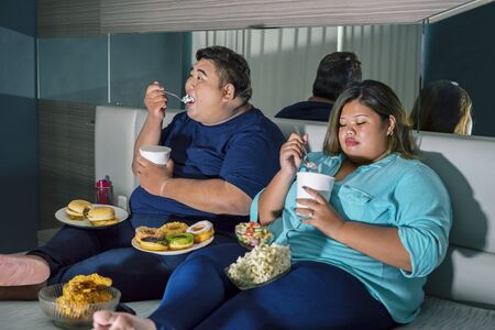 Fat Asian couple eating ice cream, while watching television with other junk foods scattered around them in their bedroom