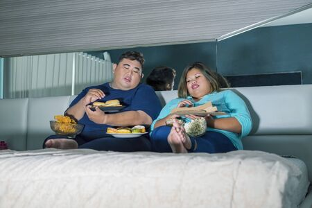 Fat Asian couple eating burger & pizza while watching television with other junk foods scattered around them in their bedroom