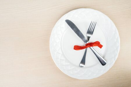 Flat layout of fork and knife taped together with a ribbon on a plate, isolated in wooden table background Stock Photo