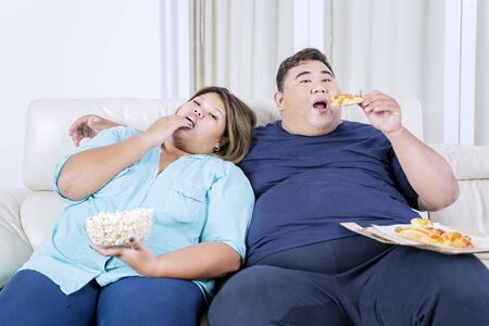 Portrait of fat Asian couple eating pizza & popcorn while watching television with boredom in their living room Zdjęcie Seryjne