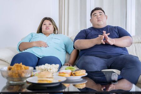 Portrait of fat Asian couple watching television, with boredom and junk foods on the table in their living room Zdjęcie Seryjne