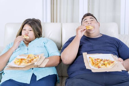 Portrait of fat Asian couple eating pizza, while watching television with boredom in their living room Zdjęcie Seryjne
