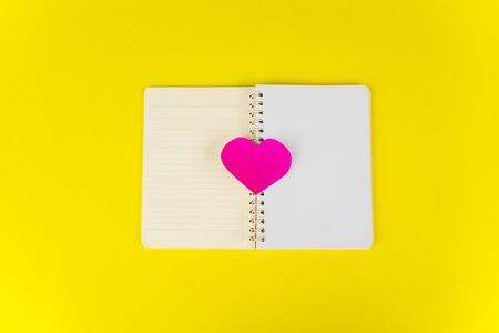 Flat layout of heart shaped card on the middle of the notebook, isolated in yellow background Stock fotó - 138254335