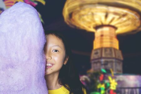 Portrait of adorable Asian girl smiling at camera happily & joyfully while hiding half of her face behind a huge cotton candy in an amusement park at night