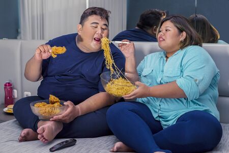 Fat Asian couple eating instant fried noodle romantically, while the fat man holding a fried chicken in their bedroom