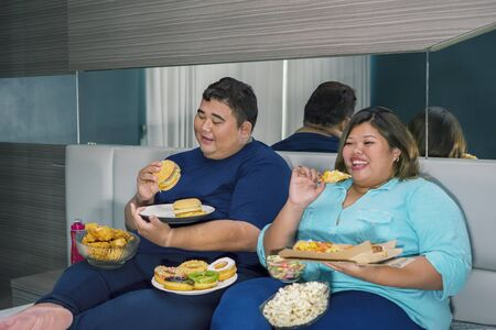 Portrait of fat Asian couple eating burger & pizza while watching television with other junk foods scattered around them in their bedroom Zdjęcie Seryjne