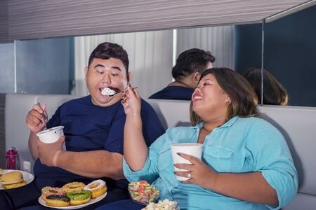 Portrait of fat Asian couple eating ice cream joyfully & romantically while watching television with other junk foods scattered around them in their bedroom
